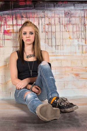 Serious blond young female sitting against graffiti wall