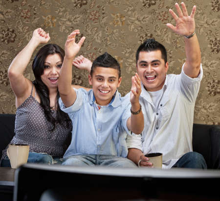 Latino family of three celebrating in front of television photo