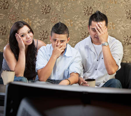 embarrassed: Disappointed Hispanic family sitting in front of television