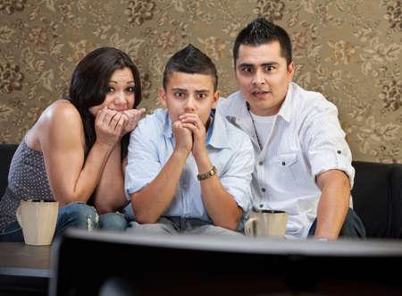 suspenso: Asustado joven familia latina viendo la televisión juntos