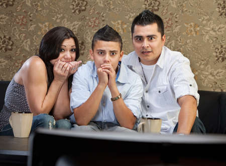 Scared young Latino family watching television together photo