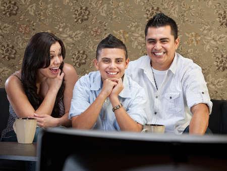 Young Latino family enjoying television indoors together photo