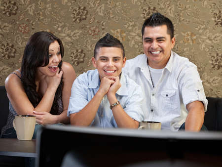 native american man: Young Latino family enjoying television indoors together Stock Photo