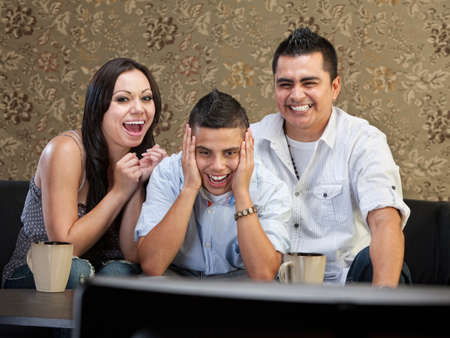 Happy family of three laughing at a television photo