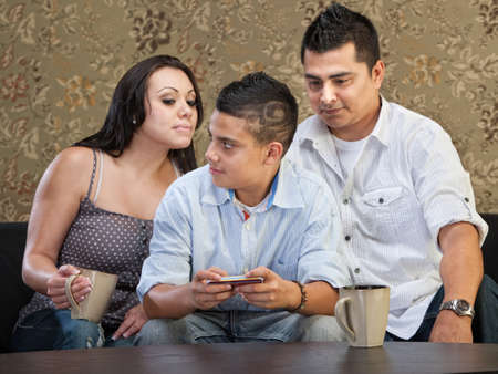 Clever Hispanic teenager watching parents watch his text messaging photo