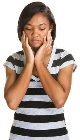 cara triste: Adolescente triste sosteniendo su cara y mirando hacia abajo