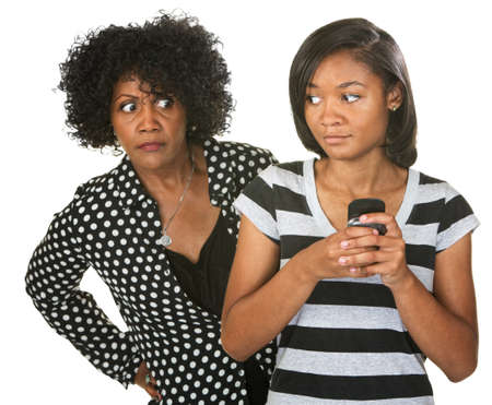 sneaking: Teenager sneaking cell phone as suspicious mother looks