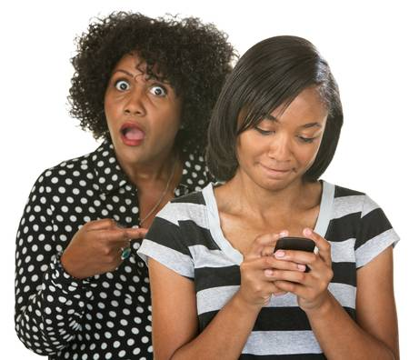 disapproving: Outraged parent behind embarrassed teen girl on phone