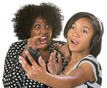 irked: Annoyed middle aged lady near loud girl with headphones Stock Photo