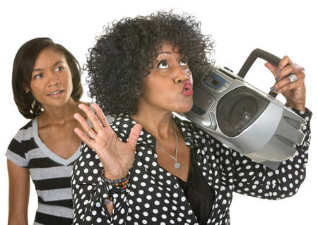 boom box: Singing middle aged woman with radio near curious teenager