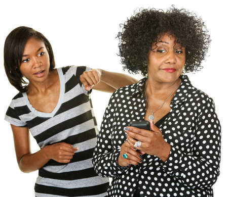 nosey: Blushing parent with phone next to nosey teenager