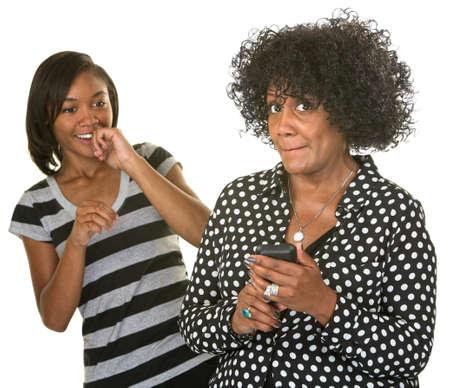 Avergonzado mujer madura con teléfono celular con adolescentes riendo