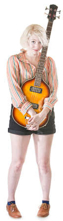 flattered: Coy blond female holding guitar on isolated background Stock Photo