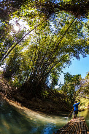 martha: Wide angle view of Black man steering bamboo boat Stock Photo