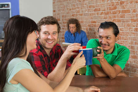 Diverse trio of friends toasting with coffee mugs photo