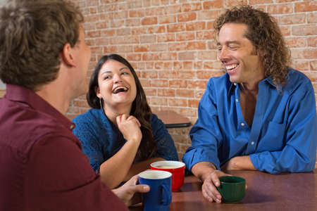 Laughing friends with coffee mugs in a restaurant photo