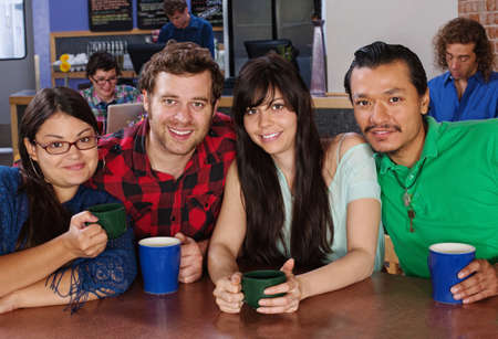 Happy diverse group of friends with coffee in cafe photo