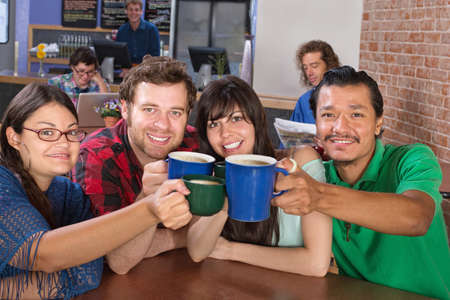 Four joyful people holding up coffee mugs photo