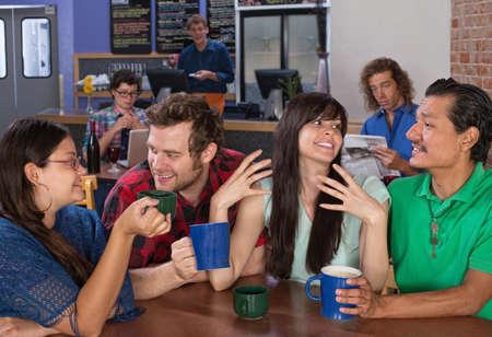 socializando: Cuatro amigos felices hablando en un café