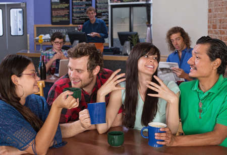 socializing: Four happy friends talking in a coffee house Stock Photo