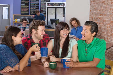 Cheerful group of people socializing in a coffee house photo