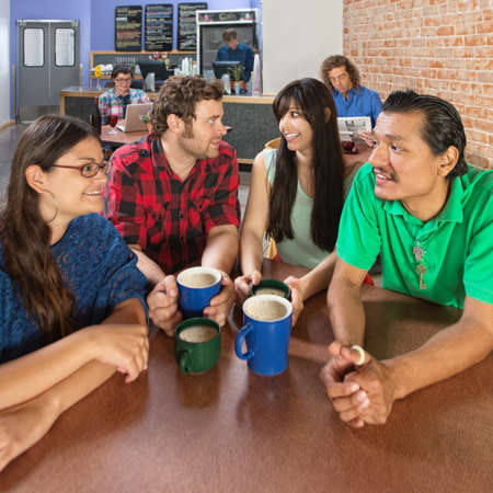 Wide angle view of four people talking in a coffee house photo