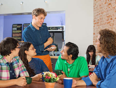 Friendly server taking orders from people in cafe photo