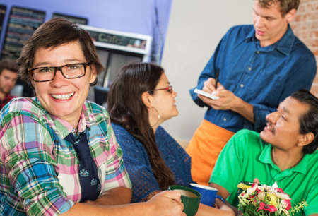 Happy young woman with eyeglasses in cafe with friends photo
