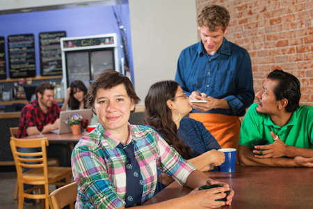 Grinning woman with friends in coffee house photo