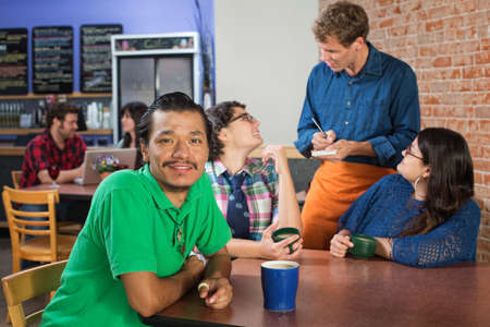 Smiling Indian man with Caucasian friends in cafe photo