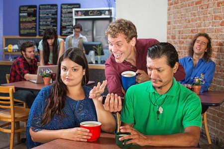 couple mixte: Couple mixte contrari�e avec l'homme montrant son t�l�phone