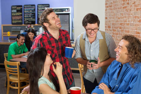 Four friends joking in a coffee house photo