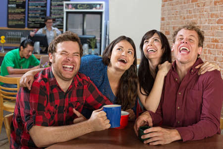 Young group of hipsters laughing hysterically photo