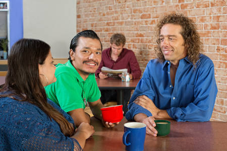 Smiling mixed group of friends drinking coffee in a cafe photo