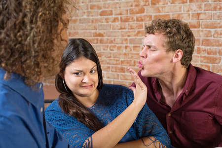 Disgusted woman pushing away man kissing her photo