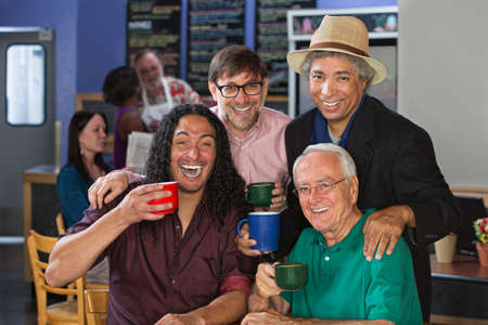 Diverse group of men celebrating in coffee house photo