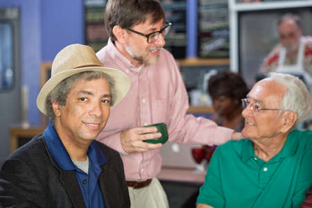 Group of mature men conversing in a coffee house photo