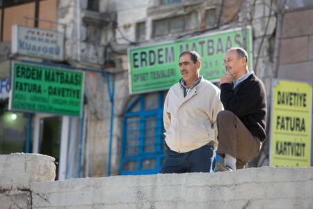 prior: ANKARA, TURKEY – APRIL 15: Men having a conversation on a city street on April 15, 2012 in Ankara, Turkey prior to Anzac Day.  Turkish men in cities and villages gather each day to discuss events of the day.