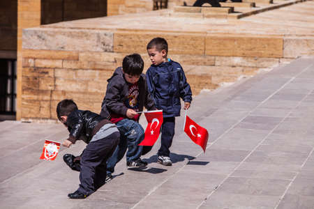 ANKARA, TURKEY – APRIL 16: Three unidentified boys prepare to honor Mustafa Kemal Atatürk, the leader of the Turkish War of Independence on April 15, 2012 in Ankara, Turkey prior to Anzac Day.  Turkish people thank and remember allies from Australia an