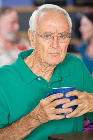 sulky: Sulky senior male holding coffee mug in cafe Stock Photo