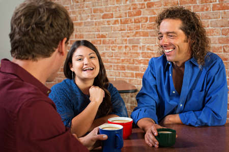 Three friends laughing and talking in coffee house photo