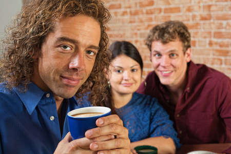Grinning man holding coffee mug in bistro photo