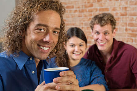 Smiling man with coffee and friends sitting together photo