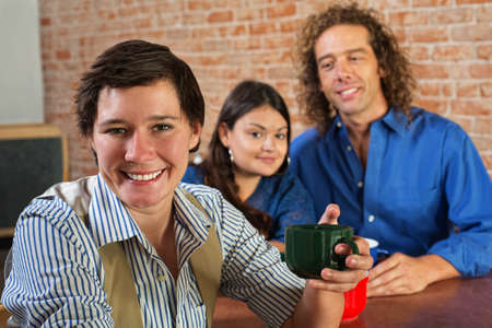 Smiling Caucasian woman holding coffee mug with friends