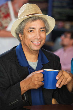 Smiling African man with hat and coffee cup photo