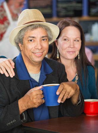 Smiling mixed couple together in coffee house photo