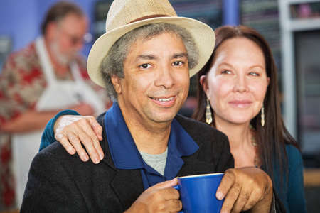 Cheerful mixed couple together in coffee house photo