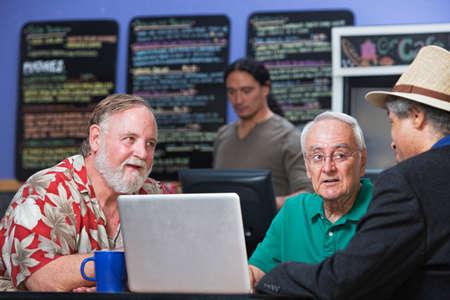 Grupo diverso de hombres maduros en caf� con el ordenador port�til photo