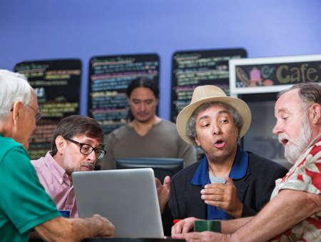 socializando: Grupo mixto de cuatro hombres maduros que habla en café Foto de archivo