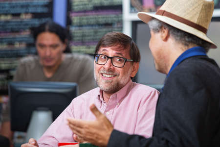 Smiling man talking with friend in a coffee house photo